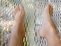 A man`s feet on a hammock - relaxation royalty free stock photography