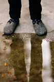 A man's feet and legs reflected in a puddle on the street. Royalty Free Stock Photo