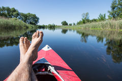 Man's  feet over canoe. Royalty Free Stock Images