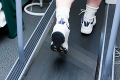 Man's feet running on treadmill. A man's feet with white and blue shoes are running on a treadmill.  Man also is wearing socks Stock Photography