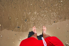 Man`s feet in the sand. Sea waves approaching beach Stock Image