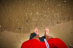 Man`s feet in the sand. Sea waves approaching beach Stock Photo