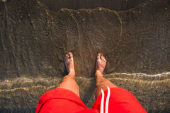 Man`s feet in the sand, waves approaching beach Stock Photo