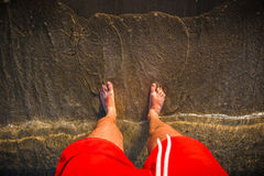 Man`s feet in the sand, waves approaching beach Stock Photos