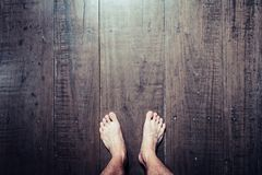 Man`s feet stand on old plank wood stock photos