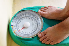 Man's feet standing on a weighing scale Stock Image