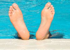 Man's feet on swimming pool background. Man's feet with bright blue swimming pool background Royalty Free Stock Photography