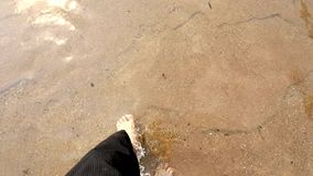 Man's feet walking in river stock video footage