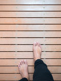 Man`s feet walking on wooden board path. In resort spa, space for text and design Royalty Free Stock Photo