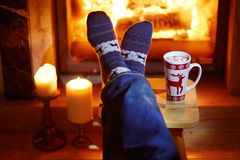Man`s feet in warm socks with large mug of hot chocolate and murshmallows near fireplace Stock Photography