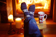 Man`s feet in warm socks with large mug of hot chocolate and murshmallows near fireplace. Cozy Christmas evening royalty free stock photo