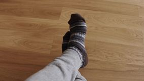 Man`s feet wearing warm knitted socks. Warm, winter and comfort concept. 4K shot stock video footage