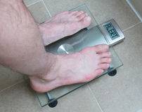 Man& x27;s feet on weight scale - Alert. Closeup of man& x27;s feet on weight scale - Alert Royalty Free Stock Photography