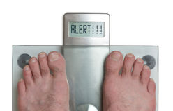 Man`s feet on weight scale - Alert. Closeup of man`s feet on weight scale - Alert Stock Image