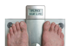 Man& x27;s feet on weight scale - Balance your life. Closeup of man`s feet on weight scale - Balance your life Stock Image