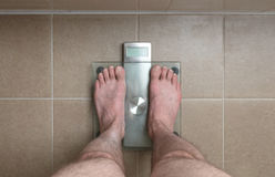 Man`s feet on weight scale -. Closeup of man`s feet on weight scale Royalty Free Stock Image