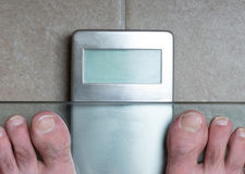 Man`s feet on weight scale -. Closeup of man`s feet on weight scale Royalty Free Stock Photos