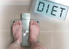 Man& x27;s feet on weight scale - Diet. Closeup of man`s feet on weight scale - Diet Stock Photography