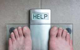 Man& x27;s feet on weight scale - Help. Closeup of man& x27;s feet on weight scale - Help Royalty Free Stock Photography