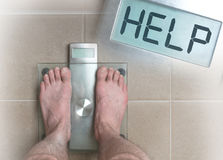 Man`s feet on weight scale - Help. Closeup of man& x27;s feet on weight scale - Help Royalty Free Stock Images