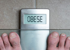 Man`s feet on weight scale - Obese. Closeup of man`s feet on weight scale - Obese Royalty Free Stock Photography