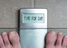 Man`s feet on weight scale - Time for gym. Closeup of man`s feet on weight scale - Time for gym Royalty Free Stock Photo
