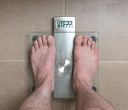 Man`s feet on weight scale - WTF!!!. Closeup of man`s feet on weight scale - WTF Royalty Free Stock Images