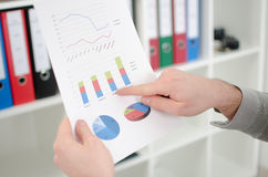 Man's finger showing business graphs Stock Images