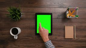 A Finger Touching an i-Pad. A man`s finger touching an i-Pad with a green screen. The i-Pad is on the brown table. View from the top. Close-up Stock Photos