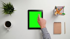 A Finger Touching an i-Pad. A man`s finger touching an i-Pad with a green screen. A tablet is on the white table. View from the top. Close-up Royalty Free Stock Images