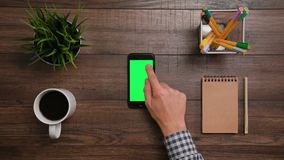 A Finger Touching a Smartphone. A man`s finger touching a smartphone with a green screen. The phone is on the brown table. View from the top. Close-up Royalty Free Stock Photos