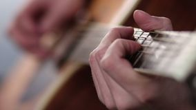 Man's fingers playing on guitar frets stock video footage