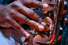 Man`s fingers press keys on his saxophone, playing live jazz, extreme closeup of a virtuoso`s hand. And musical instrument royalty free stock photography