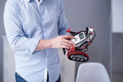 Man's fingers pressing buttons on a robot. Technology of future. Little robot being tested by a male Royalty Free Stock Images