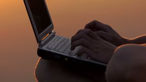 Man`s Fingers Type on a pc Keyboard Outdoor on a River Bank at Night. A Magnificent Close-Up of Male Fingers Which Type on a Gray pc Keyboard Outdoor on a River stock video footage