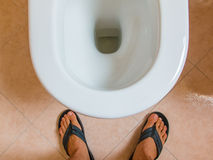 Man's flip-flops feet in front of water closet Stock Photography