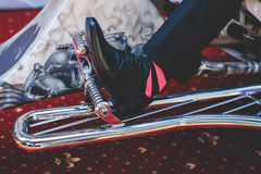 Man's foot in a leather classic shoe and striped sock stand on a Royalty Free Stock Photo