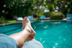 Man`s foot at pool villa. The foot of the men who sit near the pool in the resort at Pattaya. Thailand on weekend Royalty Free Stock Image