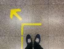 Man`s foot standing on granite floor with yellow arrow at queuin stock photos