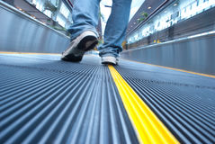Man's foot walking in airport escalator Stock Photography