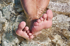 Man's foots in sea water Royalty Free Stock Photo