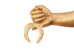 Man's golden hand with gold horseshoe Royalty Free Stock Image