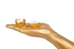 Golden hand holding eggshell on a white background. Man's golden hand holding eggshell. Isolated on a white background Stock Photos