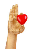 Man's golden hand with a red heart Stock Photos