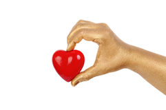 Man's golden hand with a red heart Stock Photography