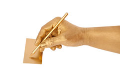Man's golden hand writes Royalty Free Stock Photo