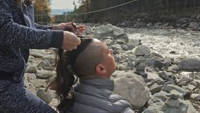 Man`s hair from pigtails. Woman braids the hair of a man. Boy does a viking hairstyle. Weave hair near a mountain river. Man`s hair from pigtails. Woman braids stock video footage