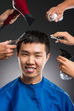 Man�s hairdo. Cropped image of stylists doing professional haircut for a young man against a grey background Stock Images