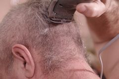 A man is cut hair on his head.The man`s hairstyle in hairdressing salon. The man`s hairstyle in hairdressing salon.A man is cut hair on his head royalty free stock photography