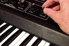Man& x27;s hand adjusting the volume on a vintage analog synth. Man& x27;s hand adjusting the volume on a vintage analog synth Stock Photos